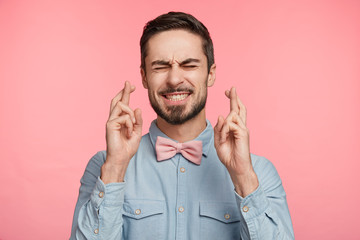 Hopeful young male with beard and mustache crosses fingers before having job interview, worries much, wish good luck, wants to produce impression on employer, wears pink tie bow and formal shirt