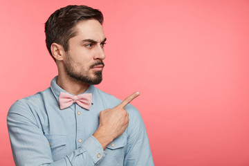 Serious strict male wears shirt and bow tie advertises something, points with fore finger at copy space of pink background. Confident man enterpreneur or manager in formal clothes models on blank wall