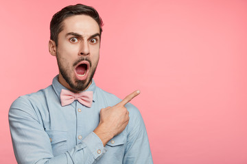 Horizontal portrait of shocked macho man with surprised expression advertises or sees something strange, can`t believe his eyes, isolated over pink background with copy space for your advertisment