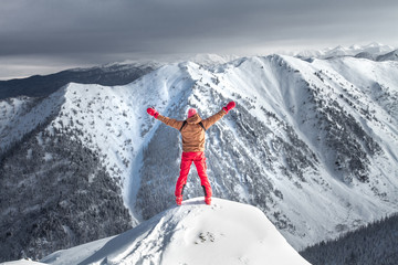A man stands on top of a mountain