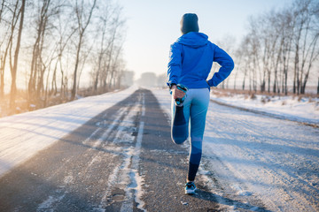 Stores à enrouleur Glisse hiver Runner stretching in winter Park. A healthy way of life.