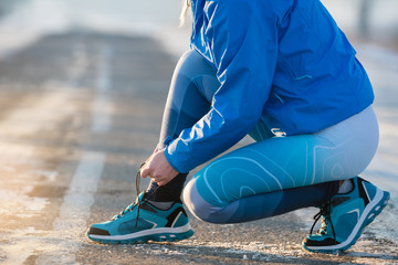 Woman runner tying shoelaces. Healthy lifestyle.