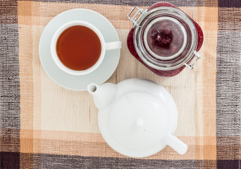 Jam, cup of tea and teapot on table