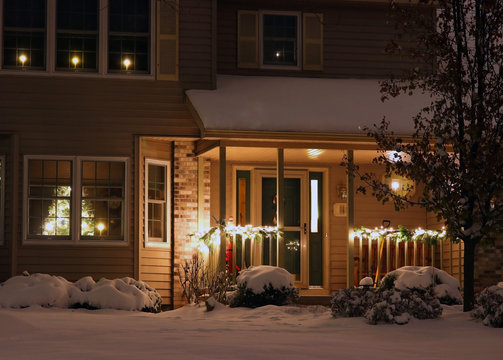 Christmas and New Year outdoor decoration background. House front porch decorated with outdoor lights for winter holidays season and glowing Christmas tree in the window.