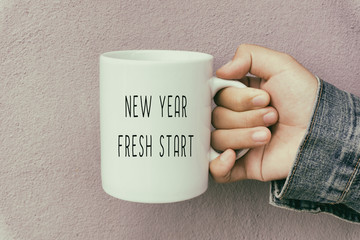 Hands Holding a Coffee Mug With Text New Year Fresh Start