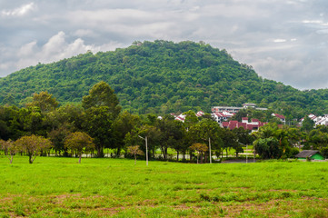Cloudy scenic view to green mountain with village