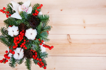 The composition of flowers and fir tree branches on wooden background