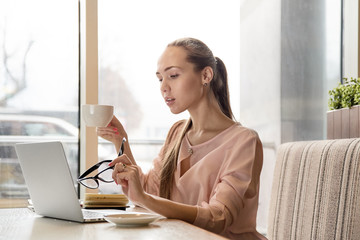 attractive young long-haired woman stylish blogger writer works with a laptop sitting at a table in a cafe with a mug of coffee and holding a glasses