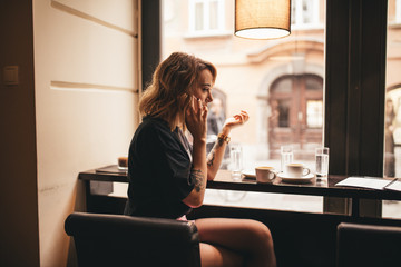 young adolescent woman in her late twenties, sitting in a bar at the window, drinking coffee and talking to a friend on a phone