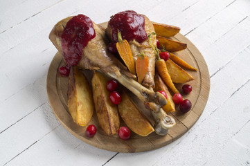 The drumstick of the Turkey with roasted vegetables and cranberry sauce.