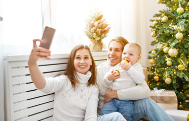 happy family photographed on phone, makes selfies in Christmas morning