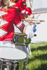 girl in red coat playing marching drum