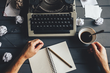 the process of writing text on paper and a typewriter with masculine hands, a creative crisis and scattered wrinkled paper