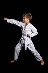 Clenched fist hit in karate. Serious kid in brand new kimono on isolated black background