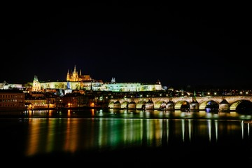 The view from the river Vltava at Charles Bridge and Prague Castle at night