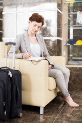 Full length portrait of elegant young businesswoman waiting in hotel lobby and making work notes sitting on sofa with suitcases