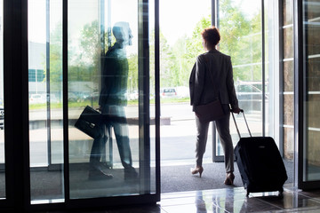 Back view silhouette of young businesswoman with suitcase walking through sliding glass doors of hotel, copy space
