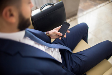 High angle close up of unrecognizable businessman using smartphone waiting in lobby with leather case