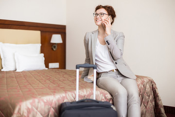 Portrait of happy young woman speaking by phone and smiling while sitting in hotel room on bed arriving for business travel, copy space