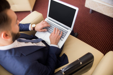 High angle of successful businessman using laptop working in hotel room or lobby, copy space