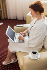 Full length portrait of elegant young businesswoman wearing bathrobe working with laptop  in hotel room enjoying business travel, copy space