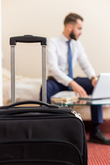 Blurred portrait of handsome bearded businessman using laptop working in hotel room, focus on suitcase in foreground