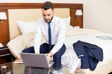 Portrait of handsome bearded businessman using laptop working in hotel room sitting on bed and enjoying business travel, copy space
