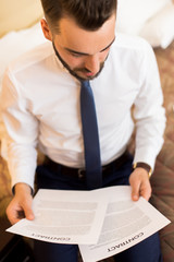 High angle portrait of young businessman working with documents sitting on hotel bed during business travel