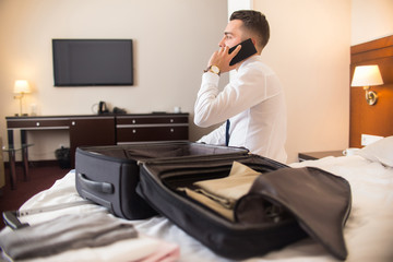 Rear view portrait of successful businessman speaking by phone after arriving to hotel while unpacking luggage