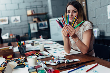 Smiling young woman holding a bunch of crayons sitting at desk surrounded by art supplies