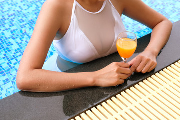 Young asian Beautiful woman relaxing in swimming pool with orange mocktail in classic glass.