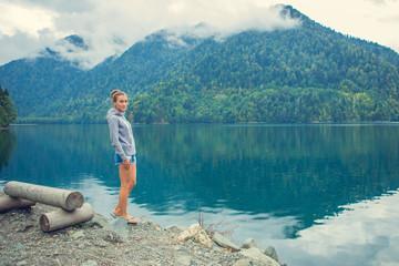 Beautiful Girl in a hoodie. Mountain blue lake green.