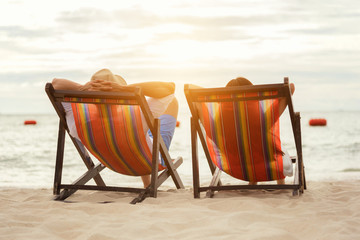 Romantic couple sitting in deckchairs at sunset