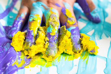 Hand and finger messy with purple and yellow paint