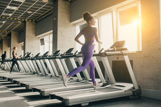 Woman running on treadmill at a panoramic window and listening to music via monitor at gym. Concept of healthy lifestyle.