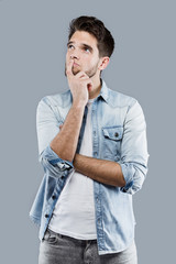 Handsome young man thinking over gray background.