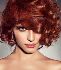 Beautiful model girl with short  red curly hair .Red head hairstyle  . Care and beauty hair products