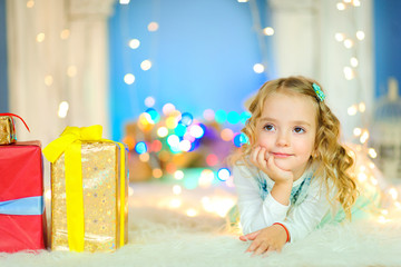 beautiful little girl lies on the floor on a white blanket and what she dreams about, there is a gift next to her, in the background festive lights.