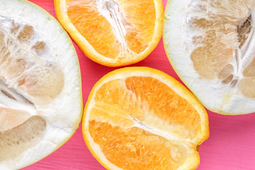 oranges and pomelo close up on a pink background. concept vitamins and summer