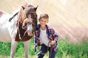 Cute little boy with horse on farm