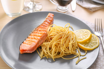 Plate with tasty grilled salmon and pasta on table, closeup