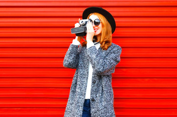 Fashion young woman takes a picture on retro camera over red background