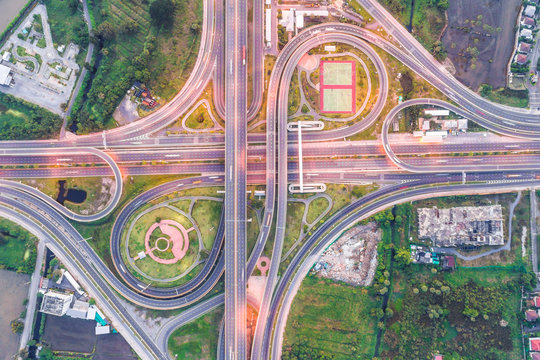 Aerial view of urbal highway intersection road with green exercise background
