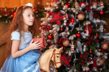 Girl with gift box near christmas tree
