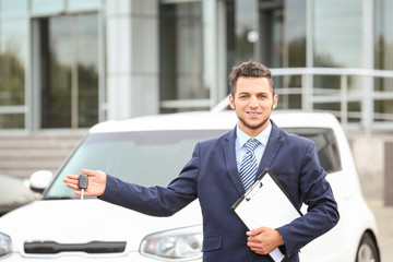 Salesman with key standing near new car outdoors