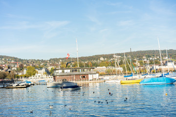 lake zurich with city buildings, boats and blue water