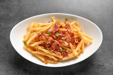 Plate with french fries and bacon on grey background