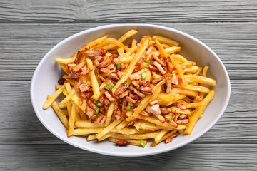 Plate with french fries and bacon on wooden background