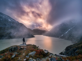 hiker on viewpoint under unreal and epic sunset sky, reflecting on glacial lake in the swiss alps