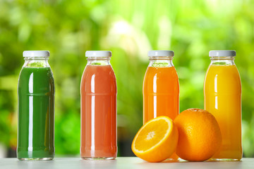 Bottles with fresh juices on table outdoors